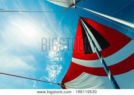 Spinnaker With Uphaul, Blue Sky In Background.