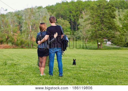 Couple hugging in standing in park view from behind.