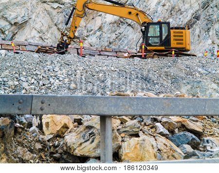 Industry. Heavy duty excavator machine digger bulldozer working on stone construction site Norway Scandinavia poster