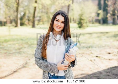 Cheerful Attractive Young Woman With Notebooks Standing And Smiling In Park