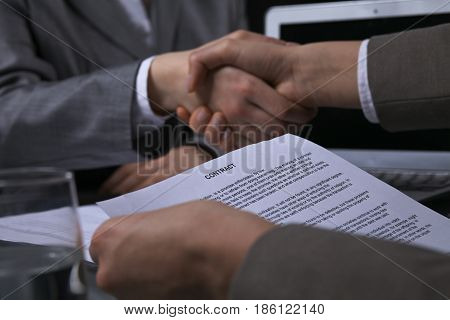 Business people shaking hands after contract signing at meeting. Low key lighting.