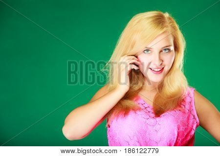 Dyeing hairstyling feminity female beauty concept. Happy blonde woman in pink top holding hand close to her face. Studio shot on green background.