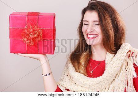 Cheerful woman holding present big red gift box. Christmas season celebration concept.