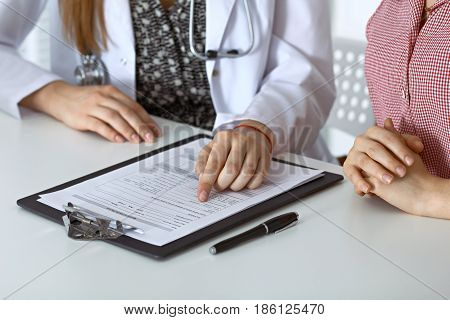 Doctor and patient sitting at the desk. Physician pointing into medical history records and explaining something to young woman. Medicine and health care concept.