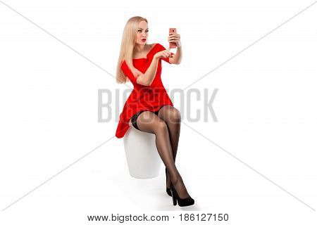 The woman in the red dress and stockings - selfie photo on the mobile phone. Isolated on white