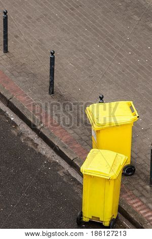 Plastic yellow wheely bins in the street outside waiting for garbage truck. Top view