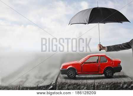 Small car covered by umbrella