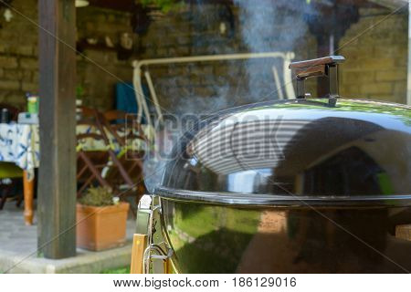 Smoke go out from a closed barbecue during pulled pork grill