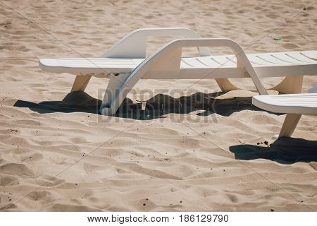 Summer objects relax and vacation concept. Empty deck chairs on sandy beach captured sunny day
