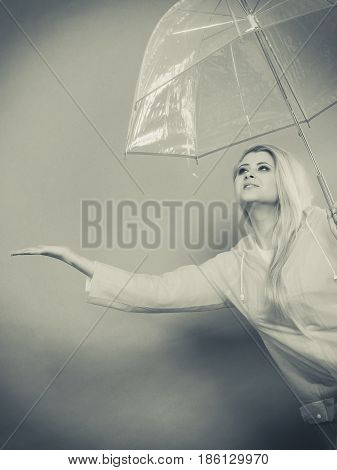 Woman Wearing Raincoat Holding Umbrella Checking Weather