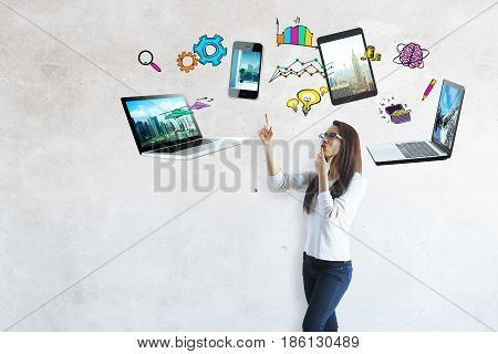 Attractive european girl with multiple devices and drawings above. Cloud computing concept