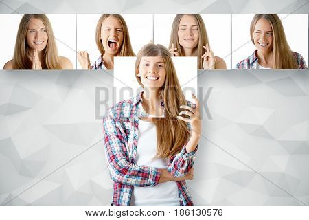 Young european girl hiding herself behind poster with smiling face. Row of faces with different expressions in the background. Emotion concept