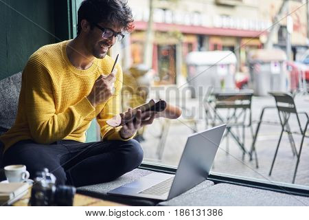 Write Ideas into personal organizer starting working day with cup of coffee sitting with laptop in cafe using free wireless connection to network