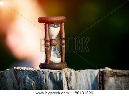 hourglass on woden stump against sun light