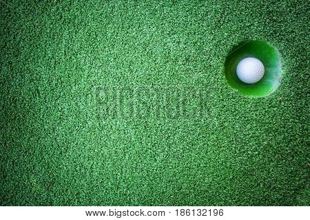 Mini golf scene with ball and hole. Can be used like background. Sunny day at resort park