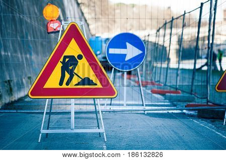 Work in progress. Roadworks, road signs. Men at work. Some signs signage for work in progress on urban street. Barriers and road signs. Silhouette of a worker at work. Right arrow.