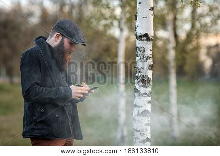 Vape Gadget Man. Outdoor Portrait Of A Young Brutal White Guy With Large Beard And In A Vintage Cap