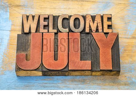 Welcome July banner - word abstract in vintage letterpress wood type blocks
