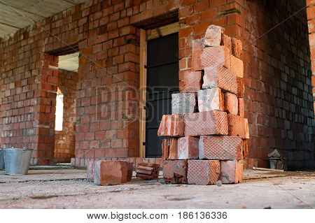 Pile of Bricks by an Old Brick Wall taken by an old building in St. Petersburg. Metal buckets on the construction site