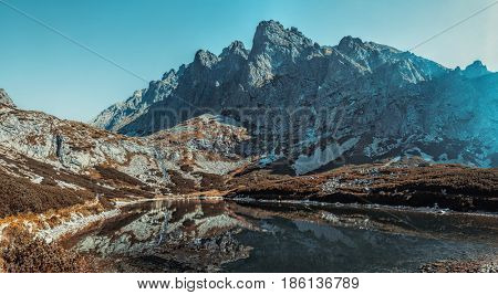 High Tatra mountains in Slovakia landscape panorama with lake. Autumn dramatic colors.