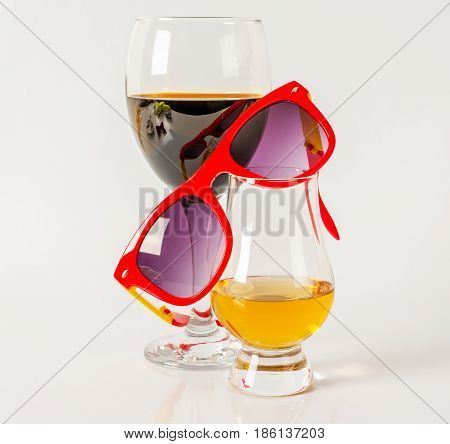 Set of single malt tasting glass and wineglass sunglasses single malt whiskey and red wine in a glass white background party set