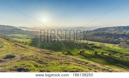 Bright Sun over Cotswold Way Valley. British Landscape at Spring from Barrow Wake Viewpoint in England