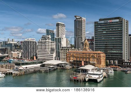 Auckland New Zealand - March 6 2017: Ferry building in front of HSBC office building seen from greenish water with a few more high rises in background under blue sky. Ferries at docks.