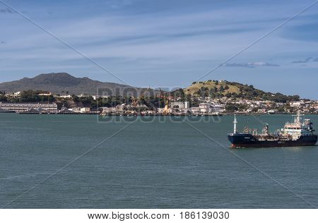 Auckland New Zealand - March 6 2017: Tanker sails in harbor in front of Devonport city under blue sky on green water. Rangitoto and Victoria volcanoes in background.
