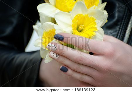 Hands Of A Young Woman With Daffodils, Manicure. Close-up