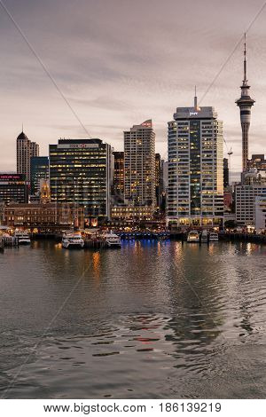Auckland New Zealand - March 6 2017: Ferry building in front of HSBC office building with Sky Tower and a few more high rises in background at sunset. Ferries at docks.