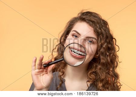 curly hair woman with brackets on biege background with magnifier