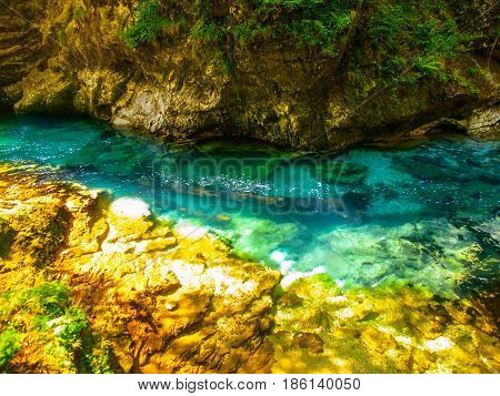Pure blue water of Radovna river in Vintgar Gorge. Natural waterfalls, pools and rapids and tourist wooden path. Slovenia, Europe.