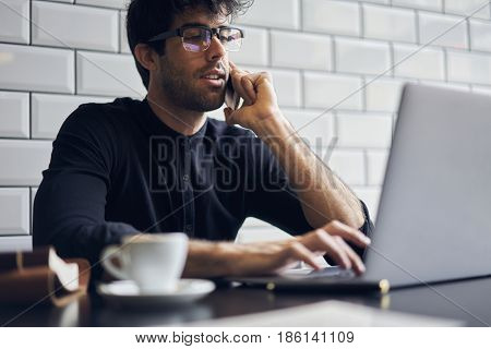 Making remote job while waiting for business meeting in cafe drinking tea sending financial report to entrepreneur laptop while talking with him on cellular call