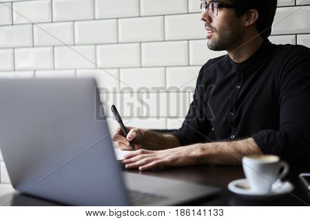 Thinking over his reportage writing down best ideas into notebook creating article for publication working hard in morning sitting in modern coffee shop interior