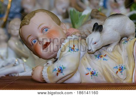 Moscow, Russia - March 19, 2017: Closeup vintage collection porcelain figurine of the Victorian era at the fair of antique hobby items. Ruddy child playing with rabbit.