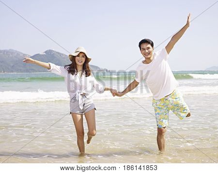 happy young asian couple having fun on beach.