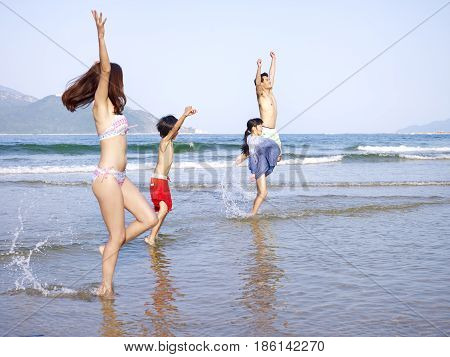 asian family with two children playing in the water on beach.