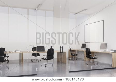 Office interior with wooden tables standing along white walls computers on them and a whiteboard above one of the desks. 3d rendering mock up