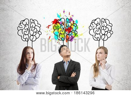 Asian businessman and his two female colleagues are standing near a concrete wall with brains drawn above them. One of the brain sketches is colorful.