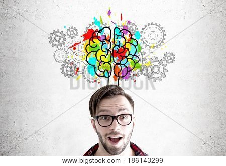 Close up of an astonished bearded young man wearing glasses and standing near a concrete wall with a colorful brain sketch surrounded by cogs