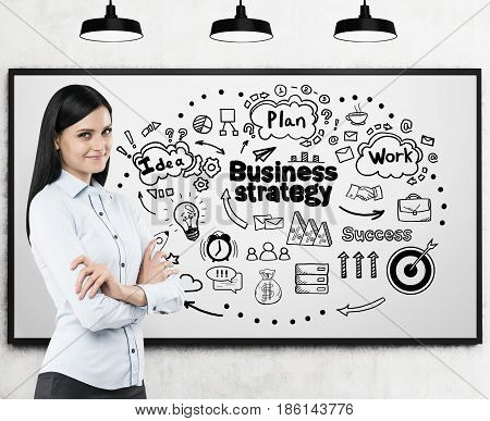 Portrait of a confident businesswoman standing with crossed arms near a whiteboard with a business strategy sketch on it.