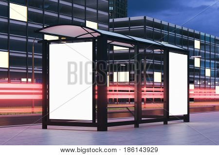 Side view of a bus stop with two blank vertical billboards standing in the night street near a building with glowing windows in the background. 3d rendering mock up