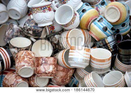 Many clay cups randomly arranged for sale
