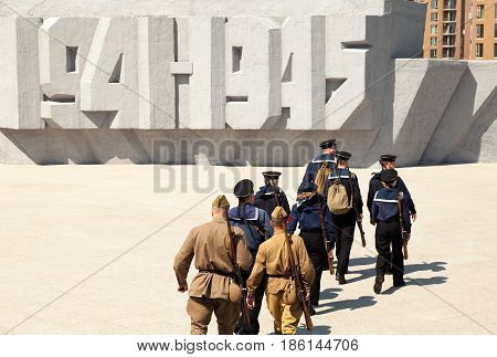 Khabarovsk Russia - May 9 2017: Group of soldiers and sailors wearing old retro USSR military uniform. Russian Victory Day celebration on May 9 at memorial 1941-1945 text on the background. Great Patriotic War reenactment