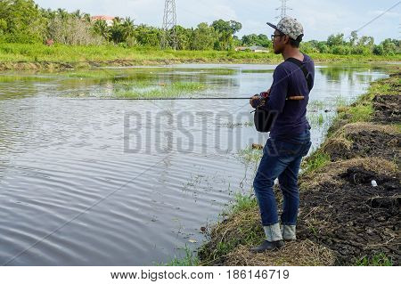 Labuan,Malaysia-May 7,2017:Young man fishing with bait casting in the Labuan river,Malaysia.Bait casting is relies on the weight of the lure to extend the line into the target area