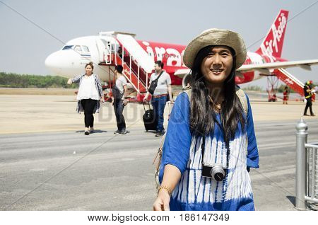 Thai Women And Traveler People Walking And Drag Luggage After Airplane Landing At Runway Go To Insid