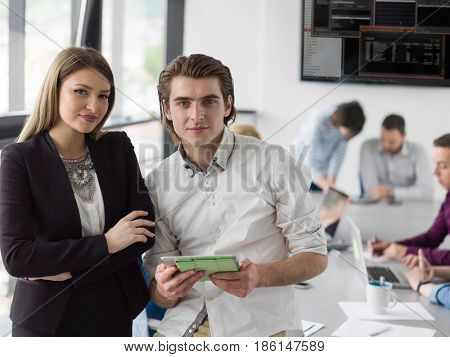 two business people using tablet  preparing for next meeting and discussing ideas with colleagues in the background