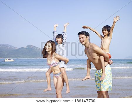 asian family with two children having fun on beach.