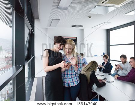 two female managers using cell telephone in office interior
