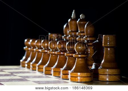Brown chess wooden pieces on chess board with dark background